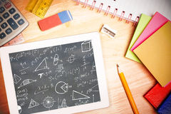 Composite image of math equations. Math equations against students desk with tablet pc royalty free stock photography