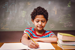 Composite image of math and science doodles. Math and science doodles against little boy writing book in classroom Royalty Free Stock Photos