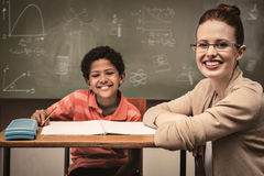 Composite image of math and science doodles. Math and science doodles against teacher assisting little boy with homework in classroom Royalty Free Stock Images