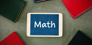 Composite image of math text on white background. Math text on white background against oberhead view of digital tablet surrounded with colorful organizers stock image
