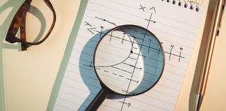 Composite image of maths pattern against black background. Maths pattern against black background against magnifying glass on notepad amidst pen and eyeglasses stock photos