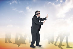 Composite image of mature businessman in a blindfold Stock Photo