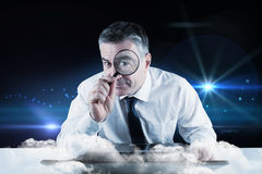 Composite image of mature businessman examining with magnifying glass Royalty Free Stock Images