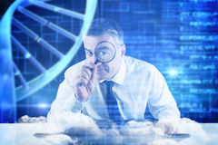 Composite image of mature businessman examining with magnifying glass Royalty Free Stock Photos
