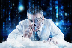 Composite image of mature businessman examining with magnifying glass Stock Photography