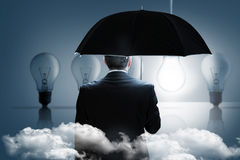 Composite image of mature businessman holding an umbrella Stock Photos