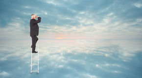 Composite image of mature businessman standing on ladder Stock Images