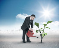 Composite image of mature businessman using watering can Stock Photos