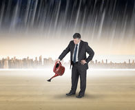 Composite image of mature businessman using watering can Stock Photography