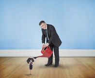 Composite image of mature businessman watering tiny businesswoman Royalty Free Stock Images