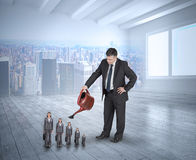Composite image of mature businessman watering tiny businesswoman Stock Photography