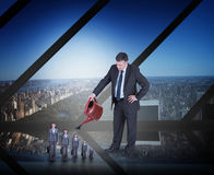Composite image of mature businessman watering tiny businesswoman Royalty Free Stock Image