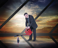 Composite image of mature businessman watering tiny businesswoman Stock Images