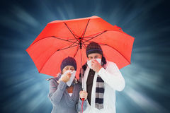 Composite image of mature couple blowing their noses under umbrella Royalty Free Stock Images