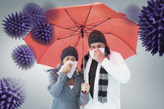 Composite image of mature couple blowing their noses under umbrella. Mature couple blowing their noses under umbrella against grey vignette stock photos
