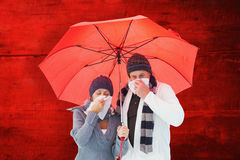 Composite image of mature couple blowing their noses under umbrella Stock Photos