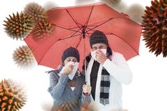 Composite image of mature couple blowing their noses under umbrella. Mature couple blowing their noses under umbrella against virus royalty free stock photography