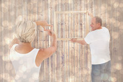 Composite image of mature couple hanging up picture frame Royalty Free Stock Photos