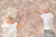 Composite image of mature couple hanging up picture frame Royalty Free Stock Images