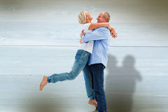 Composite image of mature couple hugging and having fun Stock Images