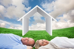 Composite image of mature couple lying and smiling Stock Image