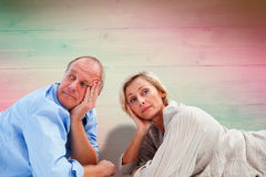 Composite image of mature couple lying and thinking Royalty Free Stock Photo