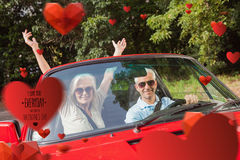 Composite image of mature couple in red cabriolet cheering at camera Royalty Free Stock Images