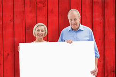 Composite image of mature couple smiling at camera holding card Stock Photography