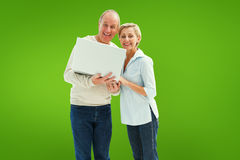 Composite image of mature couple smiling at camera with laptop Stock Photography
