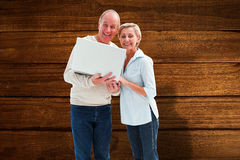 Composite image of mature couple smiling at camera with laptop Stock Photo