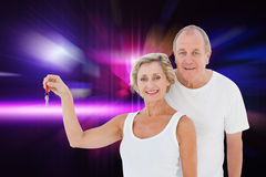 Composite image of mature couple smiling at camera with new house key Royalty Free Stock Image