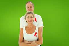 Composite image of mature couple supporting aids awareness together Royalty Free Stock Photo