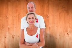 Composite image of mature couple supporting aids awareness together Stock Photos