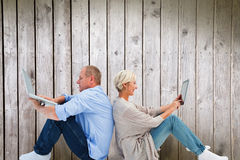 Composite image of mature couple using laptop and tablet pc. Mature couple using laptop and tablet pc against digitally generated grey wooden planks Royalty Free Stock Images