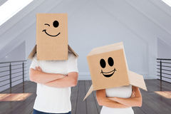Composite image of mature couple wearing boxes over their heads Stock Image