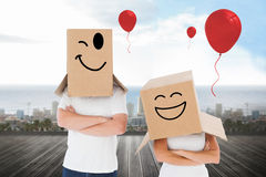 Composite image of mature couple wearing boxes over their heads Stock Photos
