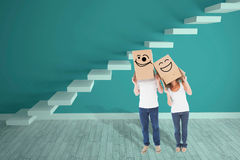 Composite image of mature couple wearing boxes over their heads Stock Photo