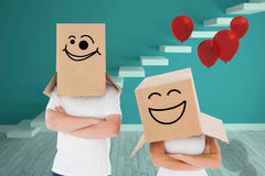 Composite image of mature couple wearing boxes over their heads Royalty Free Stock Photo