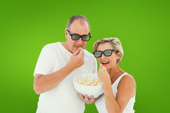 Composite image of mature couple wearing 3d glasses eating popcorn Stock Photography