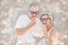 Composite image of mature couple wearing 3d glasses eating popcorn Royalty Free Stock Images