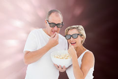Composite image of mature couple wearing 3d glasses eating popcorn Royalty Free Stock Photos
