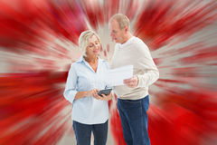 Composite image of mature couple working out their bills Royalty Free Stock Photography