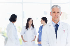 Composite image of mature doctor standing Royalty Free Stock Images