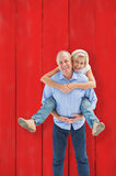 Composite image of mature man carrying his partner on his back Stock Photography