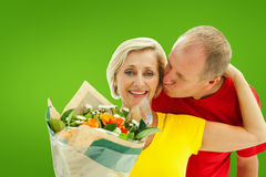 Composite image of mature man kissing his partner holding flowers Royalty Free Stock Image