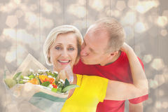 Composite image of mature man kissing his partner holding flowers Royalty Free Stock Photography