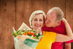 Composite image of mature man kissing his partner holding flowers Stock Photo