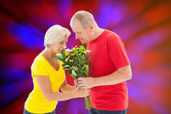 Composite image of mature man offering his partner flowers Royalty Free Stock Photo