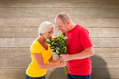 Composite image of mature man offering his partner flowers Stock Photography