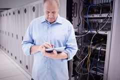 Composite image of mature man using his tablet pc Royalty Free Stock Photo